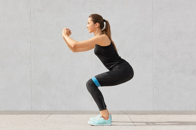 Strong sporty caucasian woman has exercises with rubber resistance band, trains legs, works on muscles, dressed in t shirt and leggings, stands indoor on grey in fitness studio