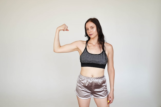 Strong sporty girl in sports top and panties showing demonstrating arms muscules on white background with copy space
