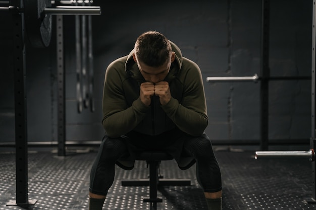 Strong sporty man sitting on gym bench suffering breakdown to overcome. demotivation sport concept.