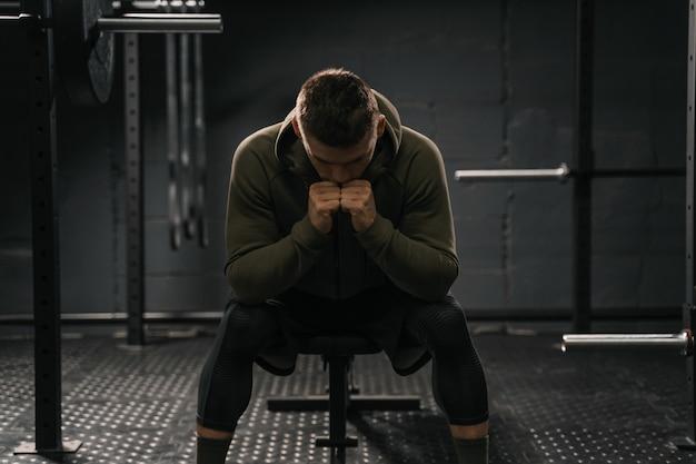 ジムのベンチに座っている強いスポーティな男性が、打ち負かすために故障に苦しんでいます。やる気低下スポーツのコンセプト。