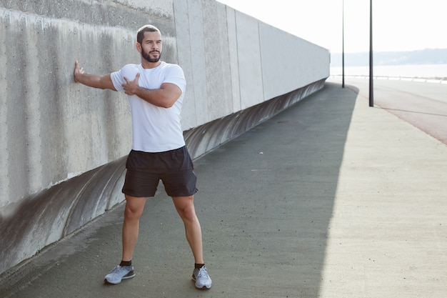 Strong sporty man stretching arm outdoors