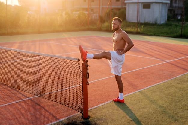 トレーニングの前に足を伸ばして強いスポーティな男。夏の暑い朝のテニスの遊び場に立っています。