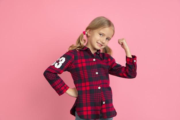 Forte, di successo. ritratto della bambina caucasica sulla parete rosa.