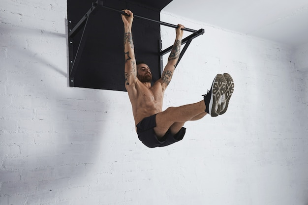 Un forte atleta tatuato mostra passo dopo passo come eseguire movimenti calistenici. la gamba intera si solleva sulla barra di trazione in posizione media