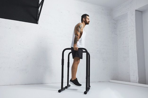 Сильный татуированный в белой майке без надписи спортсмен демонстрирует художественную гимнастику. держится на брусьях перед классическими отжиманиями, выглядит прямо.