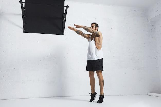 Сильный татуированный в белой майке без надписи спортсмен демонстрирует художественную гимнастику. приседания с подъемом на носки, верхняя позиция.