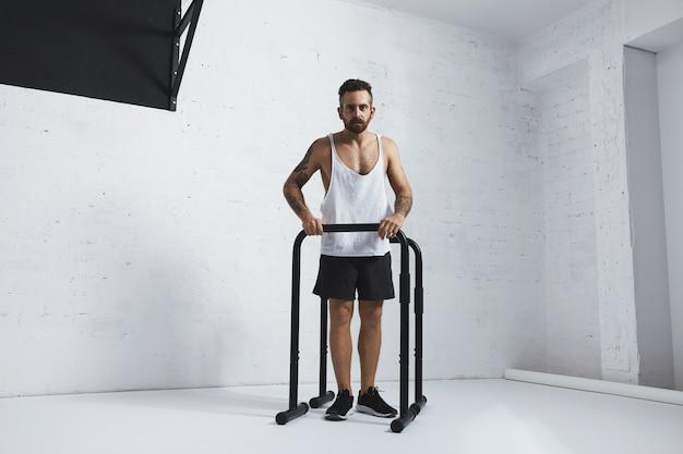 Forte tatuato in t-shirt carro armato bianco senza etichetta atleta maschio mostra movimenti calisthenic gambe estese plance push up su barre parallele
