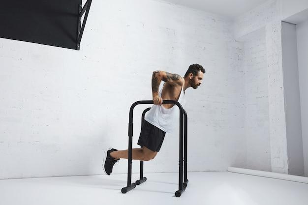 Forte atleta maschio tatuato in t-shirt carro armato bianco senza etichetta mostra movimenti calisthenic tenendo la posizione di immersione sulle barre parallele
