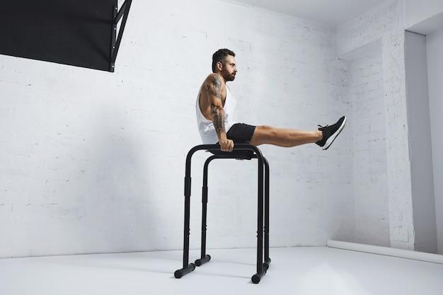 Forte tatuato in t-shirt carro armato bianco senza etichetta, atleta maschio mostra movimenti calistenici tenendo la posizione l sit sulle barre parallele