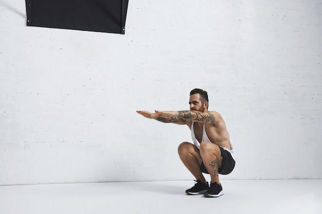 Forte tatuato in t-shirt da carro armato bianca senza etichetta, atleta maschio mostra movimenti calistenici il vitello tozzo si alza, posizione bassa