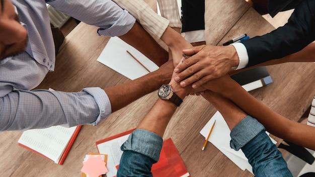 사무실에 앉아 있는 동안 손을 잡고 있는 기업인의 강력한 팀 상위 뷰