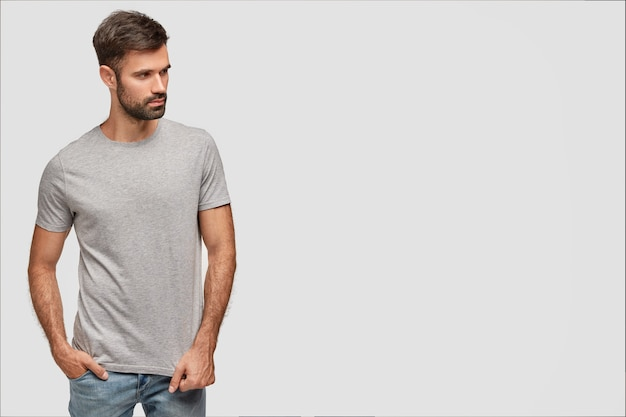 Strong thoughtful man in t shirt and jeans, advertises fashionable clothes of boutique, keeps hand in pocket