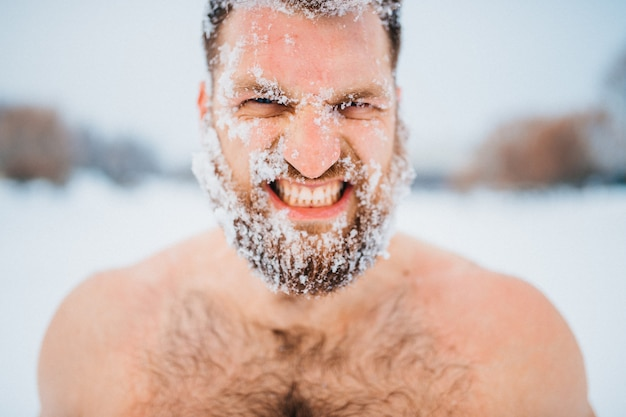 Strong topless man with angry face posing in winter