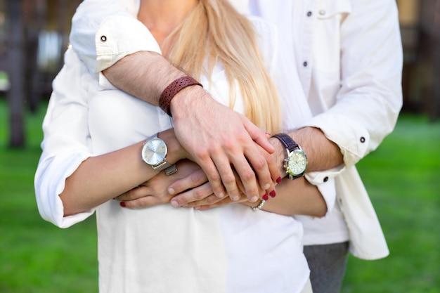 強い組合。一緒に立っている間に一緒にされている素敵なカップルの手のクローズアップ