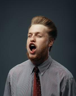 男性の顔に吹く強風、面白い感情。強力な空気の流れは、黒い背景のビジネスマンに吹く