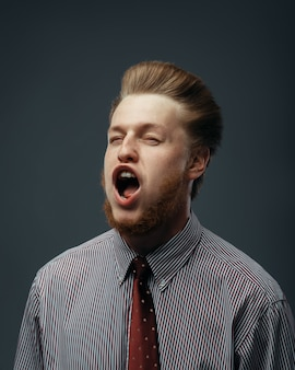 Strong wind blowing in male face, funny emotion. powerful air flow blows on businessman on black background
