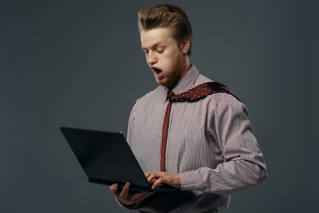 Strong wind blowing on man with laptop, funny emotion. powerful air flow blows on businessman on black background