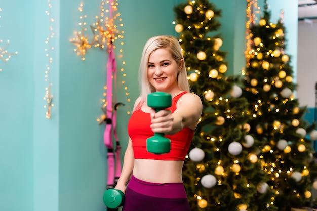 방에 있는 흐릿한 크리스마스 트리에 대해 아령으로 운동을 하는 강한 여성