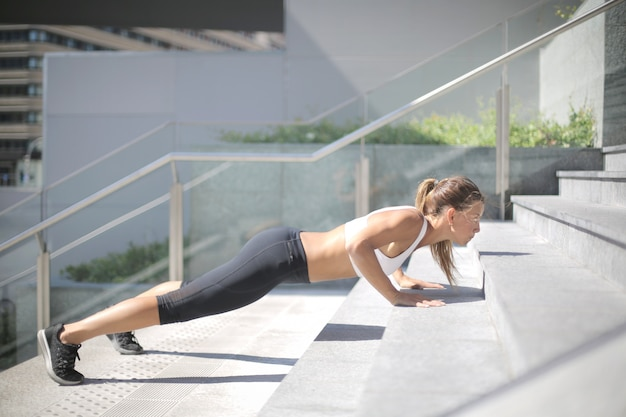 Strong woman doing push ups on the stairs
