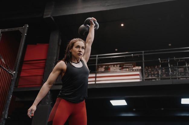 ジムでケトルベルで運動している強い女性。ファンクショナルトレーニングをしている女性