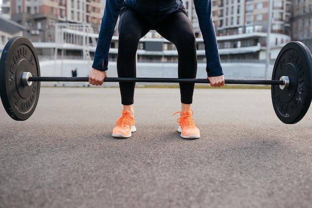 バーベルで運動する強い女性。重量挙げのトレーニングの準備をしているかわいい女の子。スポーツ、フィットネスの概念。