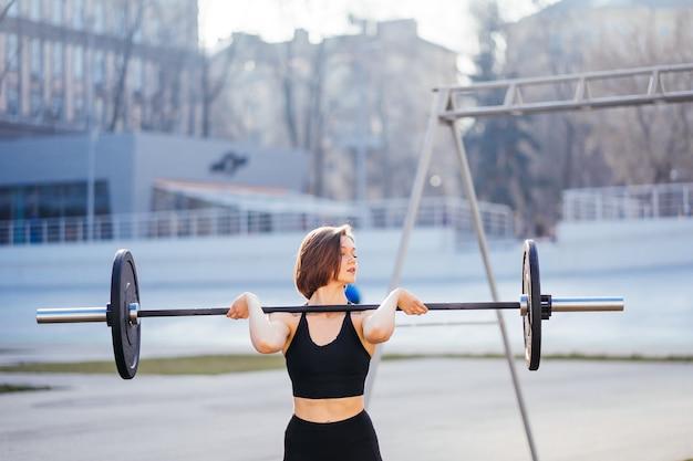 バーベルで運動する強い女性。重量挙げのトレーニングの準備をしているかわいい女の子。スポーツ、フィットネスのコンセプト。