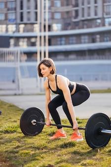 바 벨으로 운동하는 강한 여자