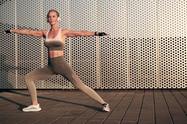 Сильная женщина в позе воина йоги вирабхадрасана ii у стены, городской фон