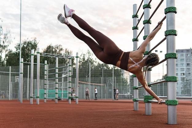 Сильная женщина делает упражнение с человеческим флагом во время художественной гимнастики