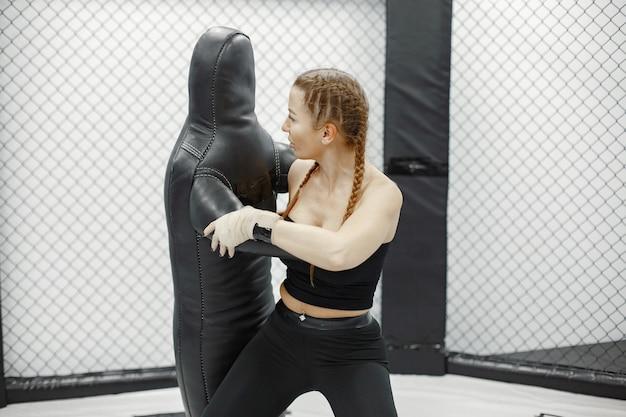 Сильная женщина тренируется с мужчиной на курсе самообороны в тренажерном зале.