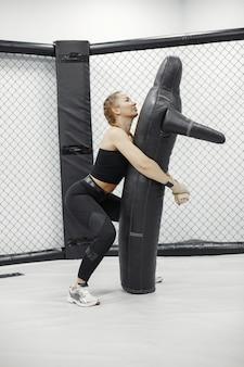 Donna forte si sta allenando con l'uomo sul corso di autodifesa in palestra.