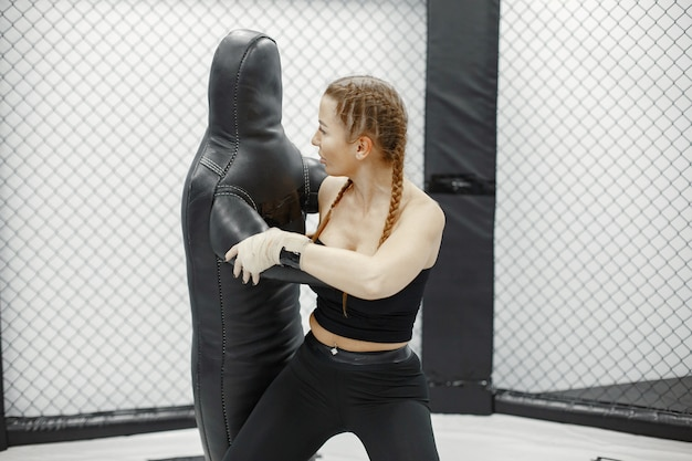 Strong woman is training with man on the self-defense course in gym.
