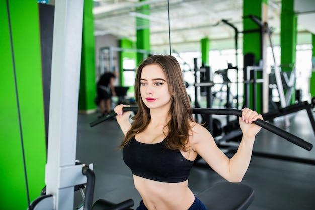 La donna forte sta lavorando con il simulatore di sport nel moderno centro sportivo di moda