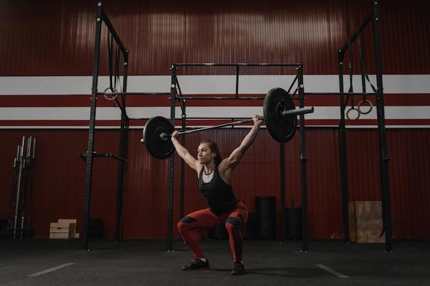 バーベルを頭上に持ち上げ、運動をしている強い女性。トレーニングジムで重いウェイトを持ち上げる若い女性に合います。