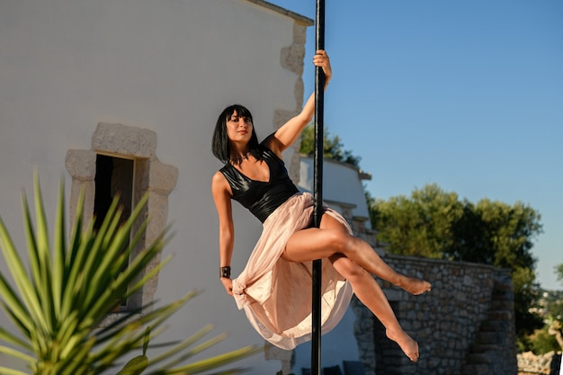 Strong woman making a pose on a pole wearing a long elegant skirt.