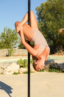 Strong woman making a pose on a pole.