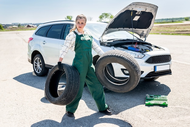 Strong woman, mechanic, posing with tyres in hands
