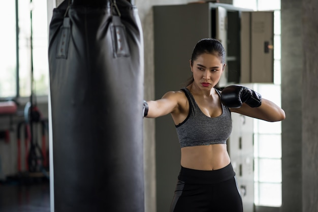 Сильная женщина практикует тайский бокс в тренажерном зале