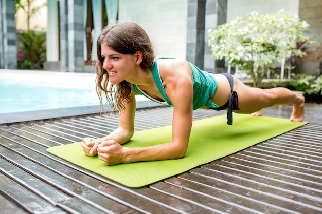 Strong woman practicing yoga in plank pose