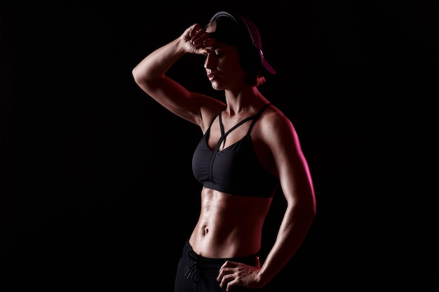 筋肉質の腹部を持つスポーツブラを身に着けている強い女性は、黒い背景の完璧な体型のヘッドフォンで音楽を聴きます