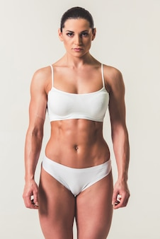 Strong woman in white underwear on light background