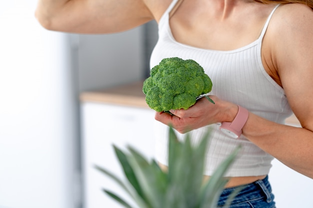 Strong woman with broccoli in the kitchen