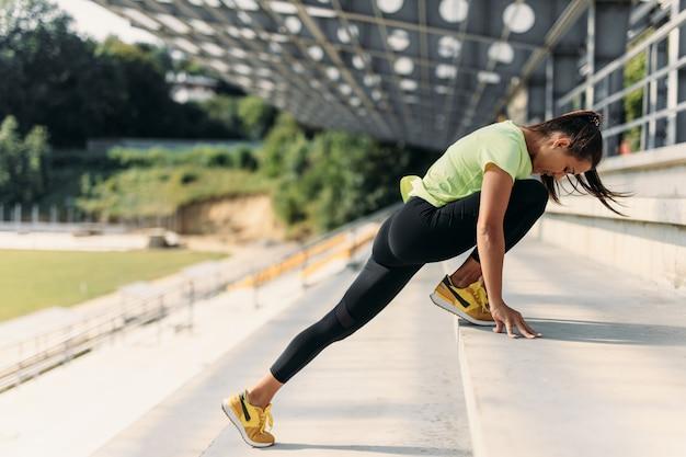 地元のスタジアムの階段で脚を伸ばしている細い体を持つ強い女性。