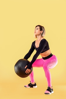 Strong woman workout with med ball. photo of sporty latin woman in fashionable sportswear on yellow wall. strength and motivation.