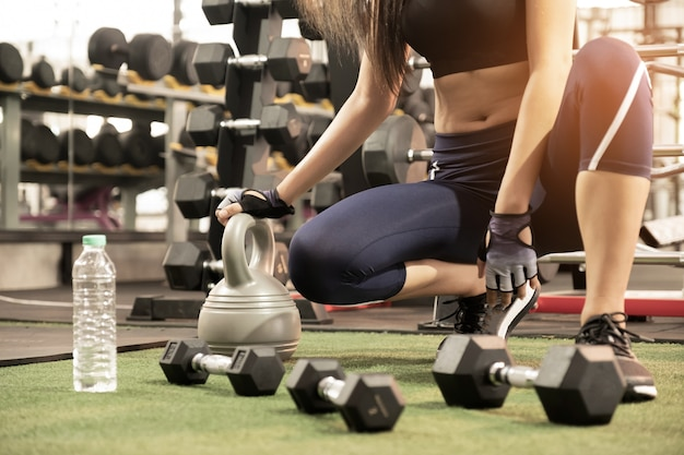 Strong women exercise in gym.she sit down, dumbbell and water in front.