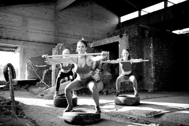 Strong women exercising at abandoned hangar. group fitness female training. black and white photo.