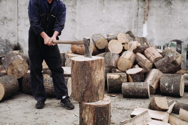 Сильный дровосек рубит дрова с острым топором