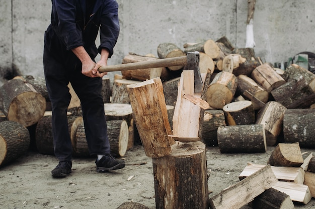 Strong woodcutter chopping wood with a sharp ax