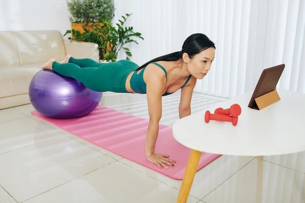 모든 근육 그룹에 맞는 볼 플랭크 운동으로 다리를 연습하고 태블릿 컴퓨터를 보고 있는 강한 젊은 아시아 여성