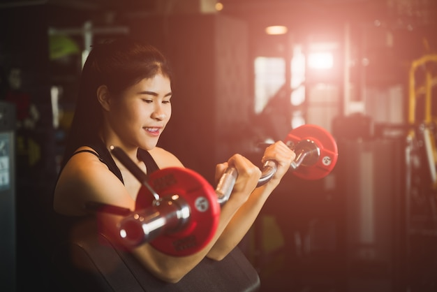 Strong young asian woman with doing exercises with barbell. fitness, bodybuilding